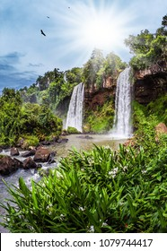 Two waterfalls from the Iguazu Falls in Argentina. Hot tropical sun illuminates the rumbling waterfalls. The concept of extreme and ecological tourism