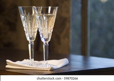 Two Waterford lead crystal champagne glasses on a dark wooden table.
