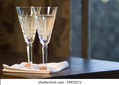 Two Waterford lead crystal champagne glasses with scallop seachells on a dark wooden table.
