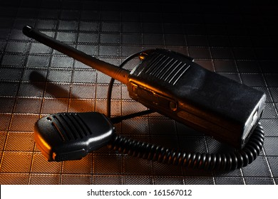 Two way radio and microphone on a textured background with orange