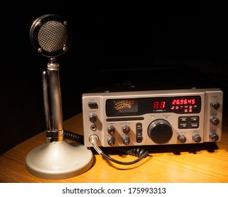 Two way radio and microphone that are on a dark desk