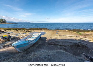 Two weathered wooden and tin row boats beached on the rocky shore of Gabriola Island with the oceans water of the Strait of Georgia in the background on a sunny summer day on the west coast of Canada