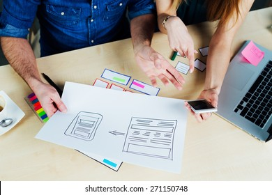 Two web designers brainstorming for ideas and sketching