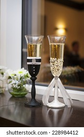Two wedding glasses decorated in the style of the bride and groom.