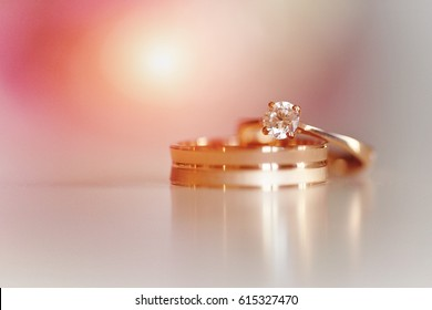 Two wedding gold rings on a pink background. Love concept. Bride and groom accessories.