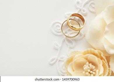 zwei Hochzeitsringe und Blumen, Einladung zur Hochzeit