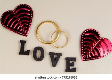Two wedding rings in gold, two pink hearts and the word love in black letters