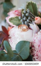 Two wedding rings lie on a bouquet