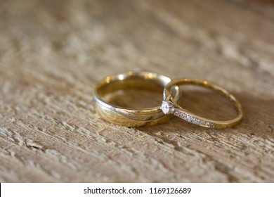 two wedding rings lying on a wooden board, one with a small diamond
