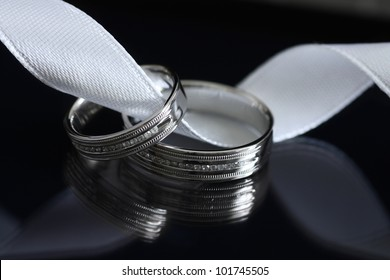 Two wedding rings made of white gold on black background with reflection