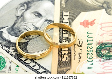 Two wedding rings and money as symbol f���¼r an expensive alliance