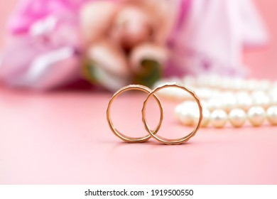 two wedding rings on a background of flowers and pearls