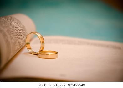 Two wedding rings on a bible page.
