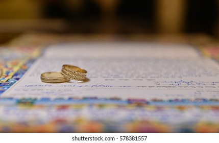 two wedding rings on a  ketubah