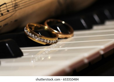 Two wedding rings on a piano and old musical notes