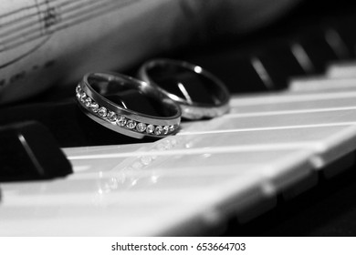 Two wedding rings on a piano, an old paper