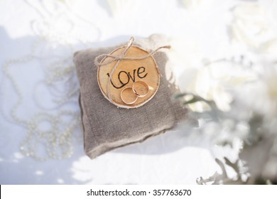 Two wedding rings on the pillow with love and spring blossoms. Wedding concept.