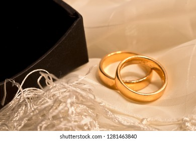 Two wedding rings on a scarf with a black box