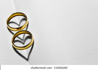 Two wedding rings on top of the blank pages that form two hearts with their shadows