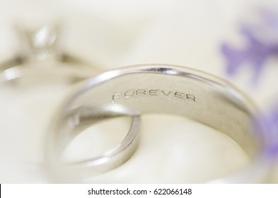 """Two wedding rings one of which is engraved with the word """"Forever""""."""