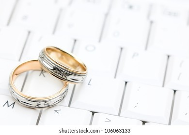Two Wedding rings sitting on a white computer keyboard