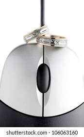 Two wedding rings sitting on top of mouse.