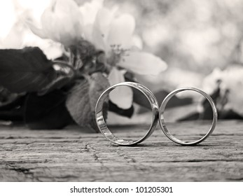 Two wedding rings and spring blossoms in black and white style