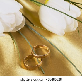 Two wedding rings and white tulips on light silk