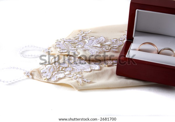 two wedding rings and woman's accessories on white