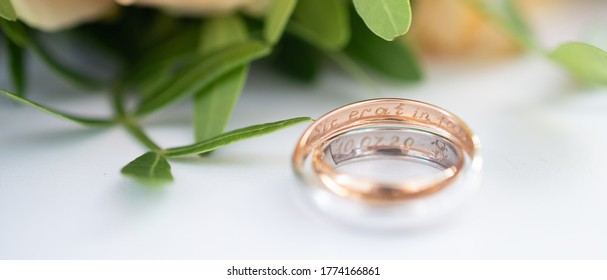 "Two wedding rings in yellow and white gold, engraved with the Latin words ""so fated"" on the background of a wedding bouquet of roses. Wedding concept, romantic greeting card. Banner"