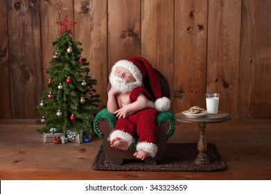 Two week old, newborn, baby boy wearing a crocheted Santa suit with beard. He's sleeping on an armchair. Shot in the studio with props, such as a Christmas tree, glass of milk and crocheted cookies.