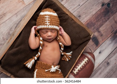 A two week old newborn baby boy sleeping in wooden crate and wearing a crocheted American football costume.