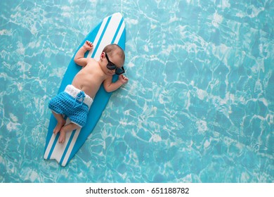 Two week old newborn baby boy sleeping on a tiny, light blue and white surfboard. He is wearing light blue, crocheted board shorts.