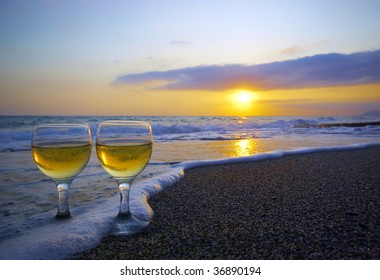 two weeping wineglasses on the sand in the wave foam and sunset