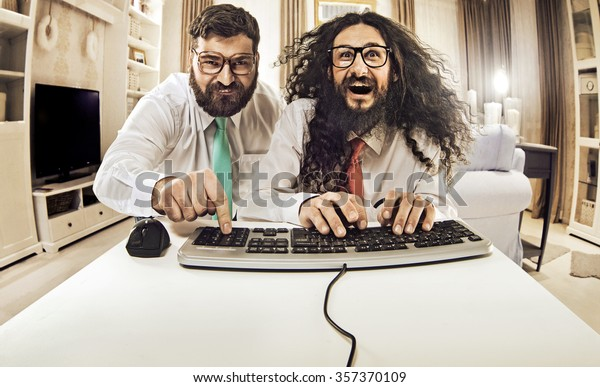 Two weird computer geeks having fun on computer