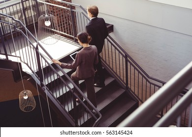 Two well dressed businesspeople climbing the staircase of the office