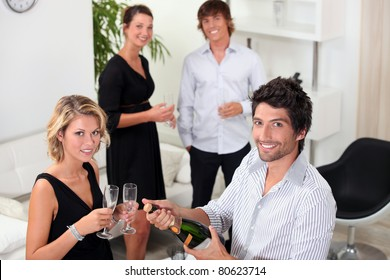 two well dressed couples drinking sparkling wine in a living room