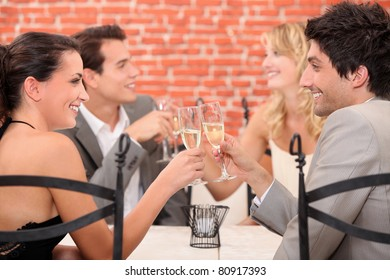 two well dressed couples toasting at the restaurant