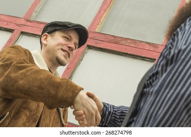 Two well dressed friends shake hands as they greet each other on a city street
