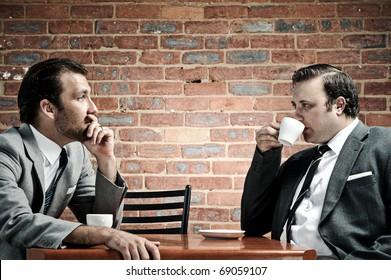 Two well dressed men in suits have coffee together, dramatic lighting