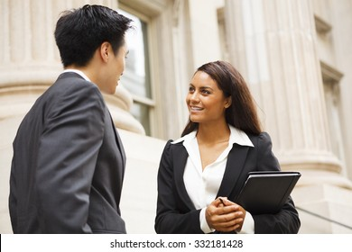 Two well dressed professionals in discussion outdoors in front of a courthouse or government building. Could be lawyers, business people etc.