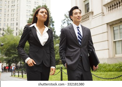 Two well dressed professionals walking down a city street. Could be lawyers, business people etc.