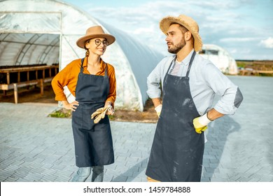 Two well-dressed farmers or agronomists standing on a farm with hothouse for snails growing on the background