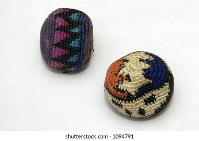 Two well-worn hacky-sack footbags against a white background.