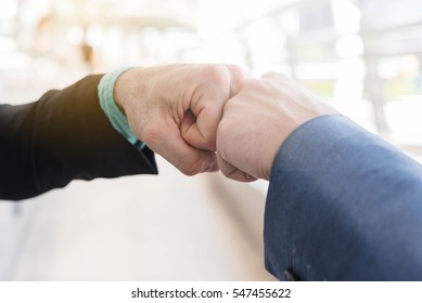 Two Westerner Business men talk and make fist bump