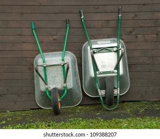 Two wheelbarrows leaning against a wall