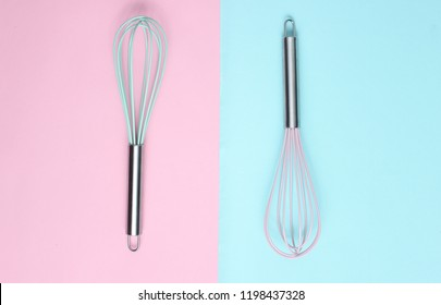 Two whisk on blue pink pastel background. Top view, minimalism