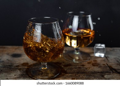 Two whiskey / cognac glasses with ice on a wooden background. Dark backdrop.