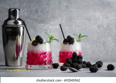 Two whiskey glasses of berry cocktails and a metal shaker. Drinks with mint and blackberries on a gray background. Copy space.
