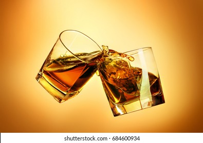 Two whiskey glasses clinking together on brown